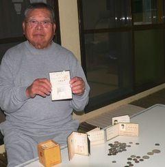 1957年に取得した映画技師の免許を手に、ドル時代の硬貨などをみせる比嘉義秀さん=名護市安和の自宅