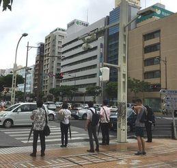 傘を手に出勤・通学する人々=13日午前8時12分、那覇市久茂地