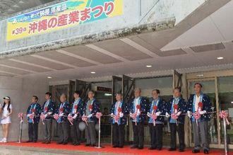 関係者のテープカットで開幕した第39回沖縄の産業まつり=23日午前、那覇市・県立武道館