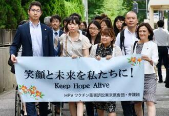 提訴のため東京地裁に向かう原告と弁護士ら=19日午後、東京・霞が関