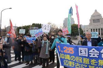 国会議事堂を包囲し新基地建設反対を訴えるヒューマンチェーンの参加者ら=25日、東京・国会議事堂前