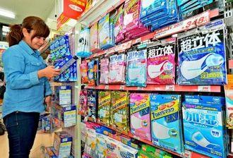 PM2・5に備え商品を手に取る女性客=15日午後、那覇市内のドラッグストア