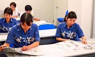 新聞を読みながら気になるニュースを探す参加者=那覇市おもろまちのJTB沖縄