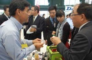 台湾企業の社員らに自社製品を紹介する出展企業の担当者(左端)=3日、沖縄セルラーパーク那覇