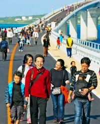 伊良部島を背に、開通前の大橋を歩く参加者=25日午前、宮古島市・伊良部大橋