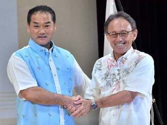 討論会を終え握手を交わす佐喜真淳氏(左)と玉城デニー氏=5日、南風原町立中央公民館