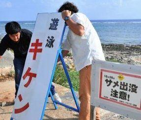 男性がサメにかまれた現場の海岸に、遊泳注意を呼び掛ける看板を設置する糸満市職員=26日午後3時30分、糸満市の大度浜海岸