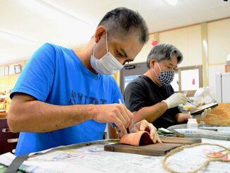 手工芸品を制作する宮城正輝さん(左)と諸見勝也さん