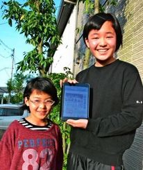 浦添商業高校野球部の新聞記事を見て「うれしすぎる。ありがとう」と喜ぶ佐藤まいさん(右)と妹のれなさん=22日、熊本県益城町