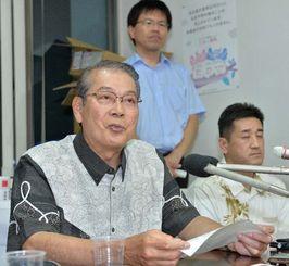 開票速報の修正について説明する沖縄県選挙管理委員会の当山尚幸委員長(左)=6日午前3時07分、県庁