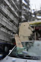 マンション建設現場の足場の板が崩れ落ち、軽自動車のフロントガラスに刺さった=29日午前、那覇市久米