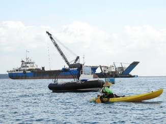 台船に土砂を積み替える運搬船に抗議する市民。フロートを乗り越え、海上保安官に拘束された=7日、名護市辺野古沖