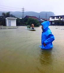 大雨の影響で冠水した沖縄県与那国町祖納の道路を歩く人=13日午前(住民提供)