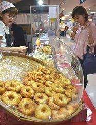 淡路島産のタマネギを使った練り天ぷらを試食する来場者ら=15日、那覇市久茂地・デパートリウボウ