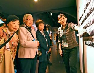 ひめゆり平和祈念資料館の説明員(右端)から展示物の説明を受ける東京大空襲の体験者ら=28日、糸満市の同資料館