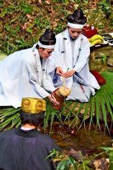 クバの葉のひしゃくで川の水をくみ、つぼに入れるノロ役=19日、国頭村辺戸(榮門琴音撮影)