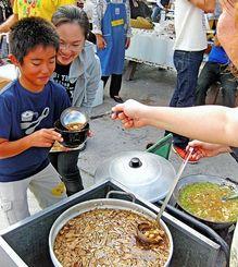熱々の芋煮を注いでもらい、笑顔を見せる親子=11月30日、宜野湾市・トロピカルビーチ