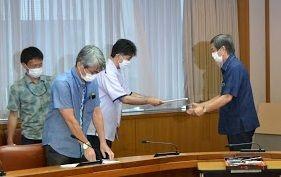 米軍ヘリの不時着について、田中利則沖縄防衛局長(右から2人目)に抗議文を手渡す謝花喜一郎副知事(右)=8日、県庁