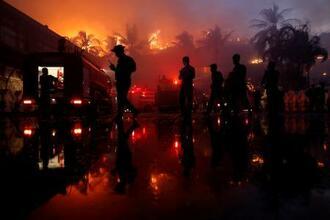 火災が起きたミャンマー・ヤンゴンのホテル前の警官ら=19日(ロイター=共同)