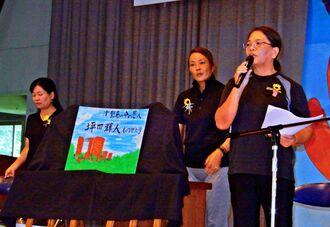 子どもたちに紙芝居「坪田輝人ものがたり」の読み聞かせをするボランティア=うるま市・津堅小中学校