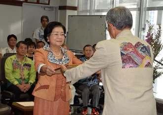 松田義之委員長(右)から当選証書を受け取る城間幹子さん=23日、那覇市役所