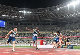 陸上東京五輪テスト大会の男子100メートル決勝でゴールする、(左から)3位の小池祐貴、優勝したジャスティン・ガトリン、2位の多田修平。緊急事態宣言下、無観客で行われた=9日夜、国立競技場