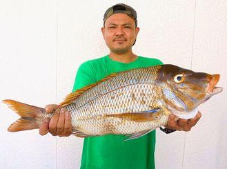 読谷海岸で64センチ、3.2キロのタマンを釣ったチームビンボーレンジャイの与古田真市さん=21日