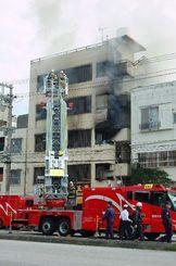 5階建てアパートの3階部分から出火し、消火する消防隊員ら=18日午前10時50分ごろ、那覇市曙