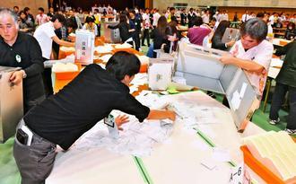 開票作業を行う那覇市の職員ら=24日午後9時11分、那覇市民体育館