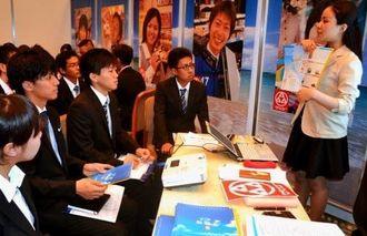 担当者の話に耳を傾ける学生ら=17日、宜野湾市・沖縄コンベンションセンター
