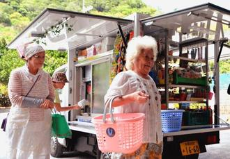 JAおきなわの移動購買車「あじまぁ号」での買い物を楽しむ地域住民=24日、大宜味村・喜如嘉公民館前