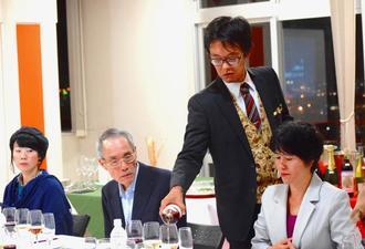参加者のテーブルにワインを注ぐソムリエの吉川太朗さん=25日、北中城あやかりの杜図書館