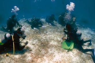 沖縄海洋工機開発の水中音声無線機器を使ってインストラクター(右)から指導を受けるダイビング客ら(提供)