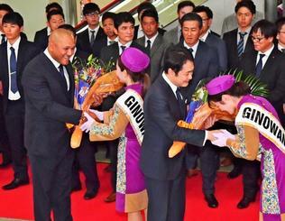 花束を受け取るDeNAのアレックス・ラミレス監督(前列左)ら=那覇空港