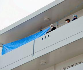 女性が殺害されたアパートで捜査する警察官ら=4月13日、北谷町