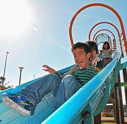 照りつける太陽の下で、元気に遊ぶ子どもたち=30日午後3時ごろ、豊見城市・豊崎にじ公園