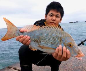 恩納村海岸で56センチ、2・5キロのタマンを釣った大嶺彪馬さん=21日