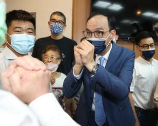 台北の国民党本部を訪れ、関係者にあいさつする朱立倫氏(右)=25日(中央通信社=共同)
