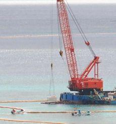 クレーンを使ってコンクリートブロックを海中に沈める大型作業船=1日、名護市の大浦湾