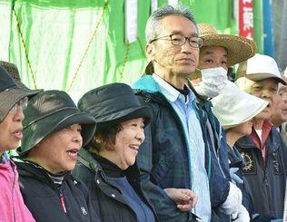 屈してはならないー。土砂投入を前に、ほほ笑みながら腕を組んで抗議する女性=14日午前、名護市辺野古