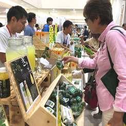 「シークヮーサーの日」関連イベントで商品を手に取る買い物客ら=22日、サンエー那覇メインプレイス