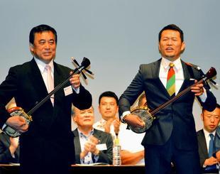 記者発表会で三線を披露する仲本光正さん(手前左)と須藤元気さん=20日、東京・銀座のヤマハ銀座スタジオ