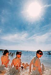 照りつける太陽の下、海辺で日光浴を楽しむ観光客=1日、豊見城市・美らSUNビーチ(喜屋武綾菜撮影)