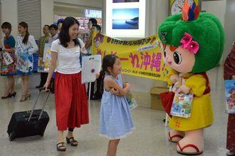 県内各地の観光キャンペーンレディーとゆるきゃらが到着客を出迎えた=1日、那覇空港国際線ターミナル