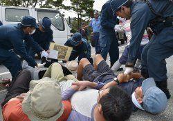 北部訓練場への資材搬入に抗議し座り込む住民を排除する県警機動隊員=12日午前9時すぎ、東村高江