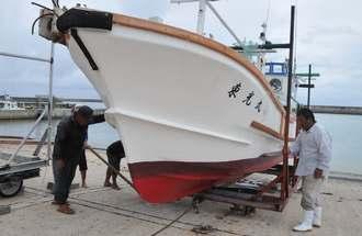 突然の台風接近で漁を切り上げ、漁船を陸揚げする漁師ら=2日、石垣市・登野城漁港