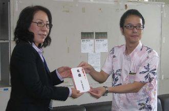 「らい君を救う会」役員の屋比久さんに寄付金目録を手渡す川満副委員長(右)=8日、県庁