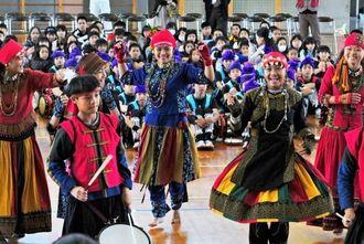 与那原小学校6年生児童との交流会で、台湾先住民・パイワン族の伝統舞踊を披露する泰武中学校(台湾)の生徒たち=与那原小学校