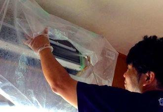 高圧洗浄器で水を拭きかけ汚れを落とす安里さん