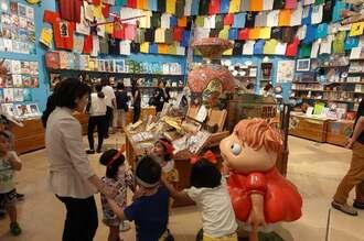 映画などの宣伝材料も展示している「ジブリの大博覧会」。内覧する関係者ら=12日、那覇市の県立博物館・美術館 ⓒStudio Ghibli